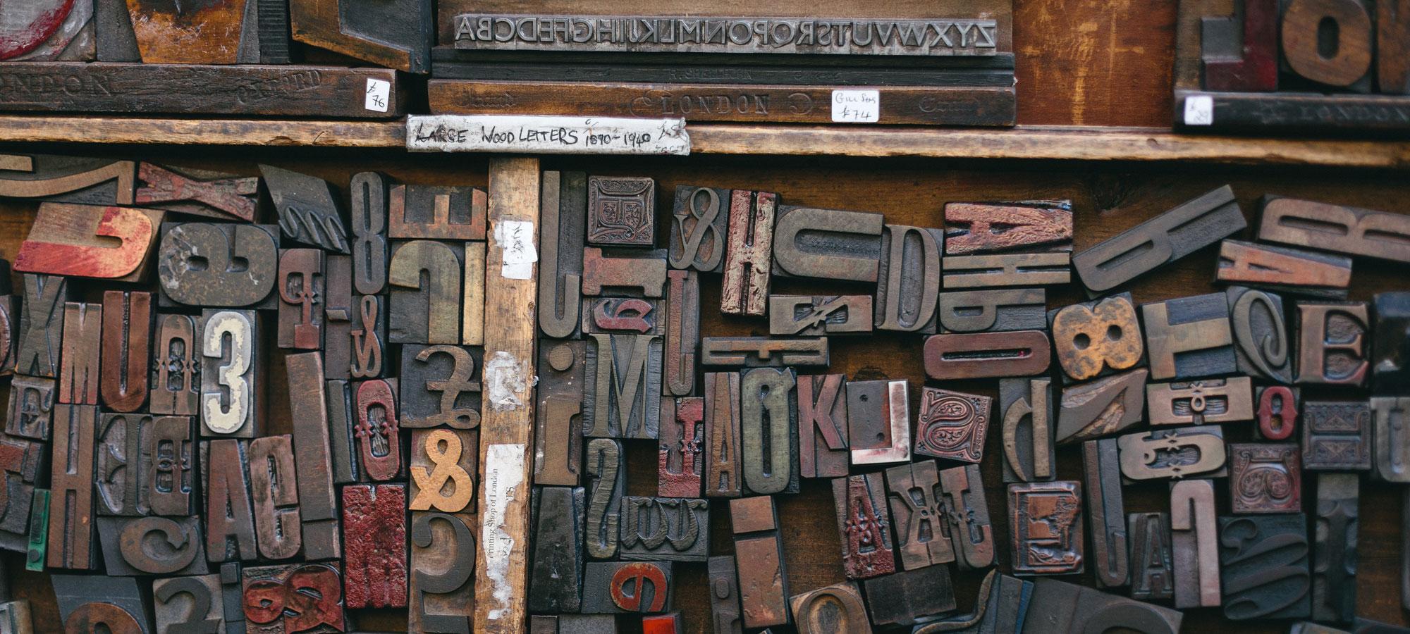 hözerne Druckbuchstaben im Regal, © unsplash